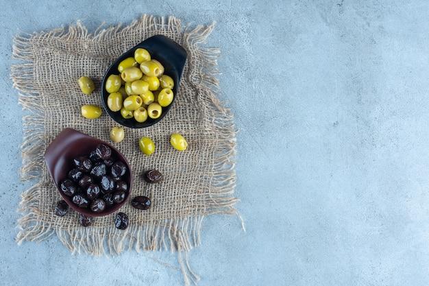 Miski oliwek zielonych i czarnych na marmurze.