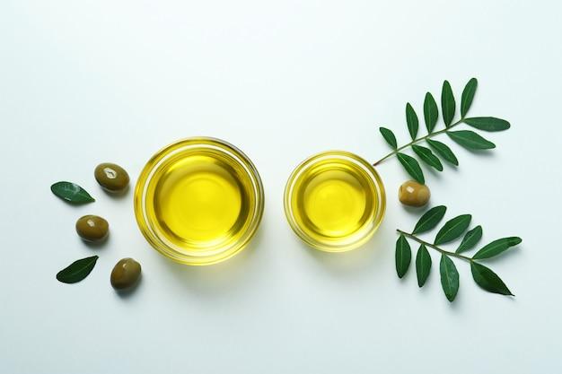 Miski oliwy, oliwki i gałązki na białym tle