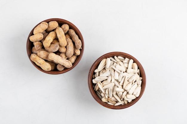 Miski organicznych orzeszków ziemnych w łupinach i orzeszków ziemnych na białej powierzchni