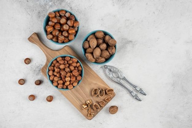 Miski orzechów włoskich, orzechów laskowych i jąder na drewnianej desce do krojenia.
