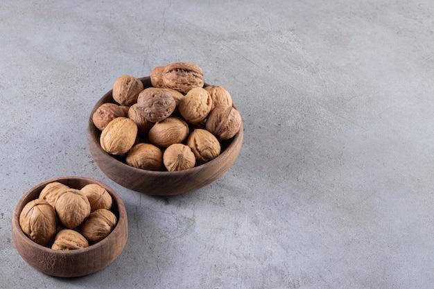 Miski pełne zdrowych orzechów włoskich w łupinach ustawione na kamiennym stole.