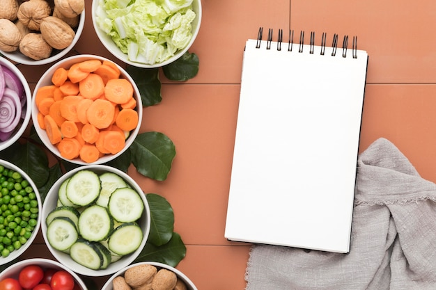 Miski pokrojonych warzyw z notatnikiem i szmatką