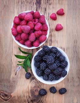 Miski przepełnione letnimi jagodami, takimi jak maliny i jeżyny.