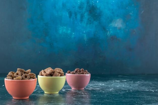 Miski różnych zbóż, na niebieskim tle. zdjęcie wysokiej jakości