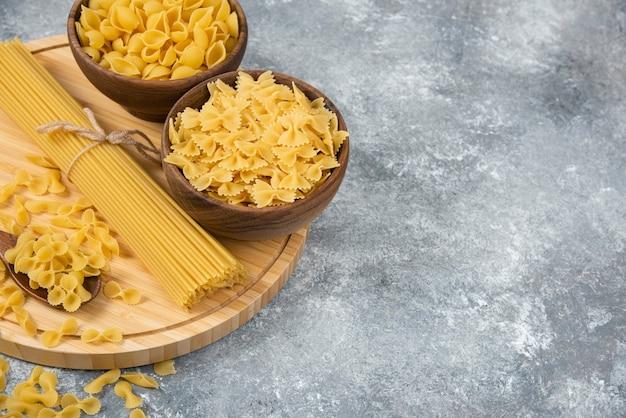 Miski surowego suchego makaronu i spaghetti na marmurowej powierzchni.