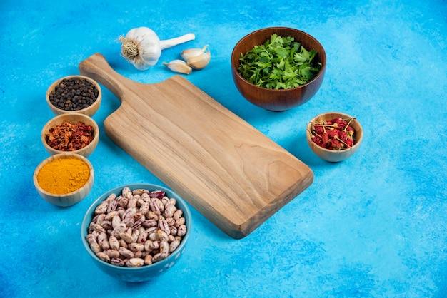 Miski surowej fasoli i organicznych przypraw na niebieskim tle.