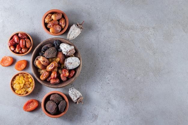 Miski suszonych daktyli organicznych, persimmons i rodzynek na tle kamienia.