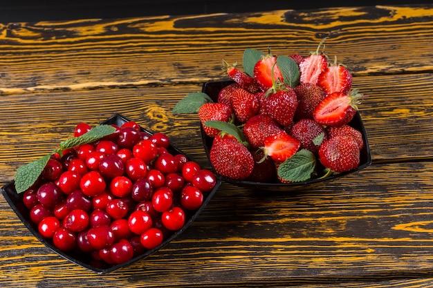 Miski świeżych oczyszczonych jagód gotowe na pyszny letni deser z truskawkami i wiśniami przyozdobionymi miętą podawane w miskach na drewnianym stole