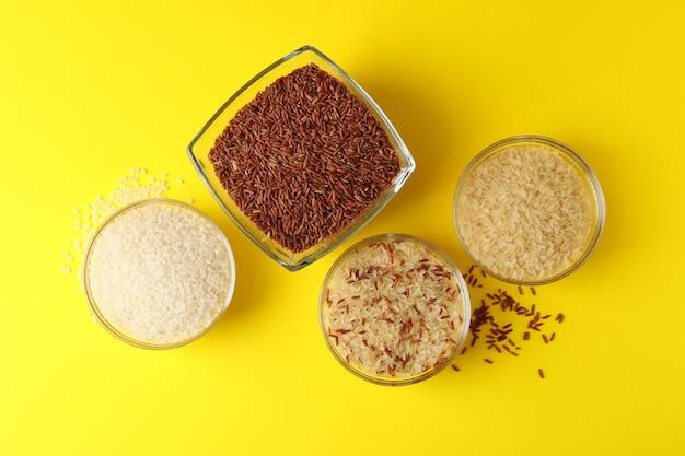 Miski z innym ryżem na żółtej powierzchni