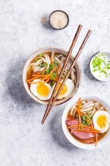 Miski z japońską zupą ramen, pałeczkami, białym rustykalnym tłem betonu.