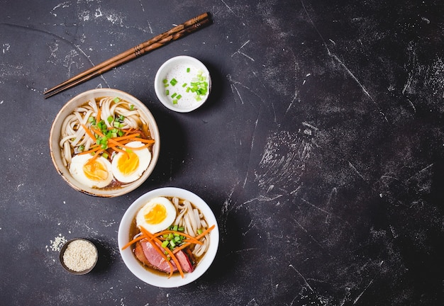 Miski z japońską zupą ramen, pałeczki do jedzenia, rustykalne tło z czarnego betonu.