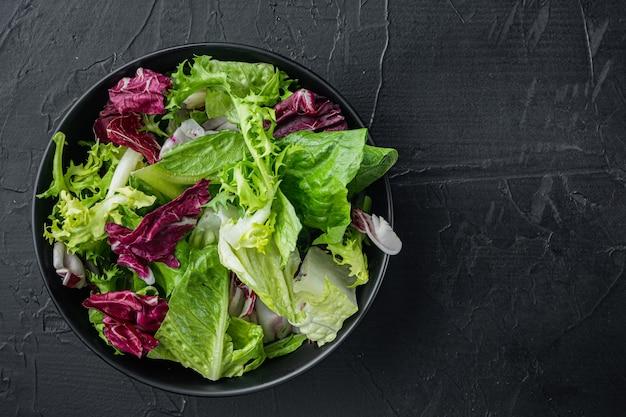Miski z mieszaną rozdrobnioną sałatą sałatową ze świeżymi liśćmi, na czarnym stole, widok z góry na płasko