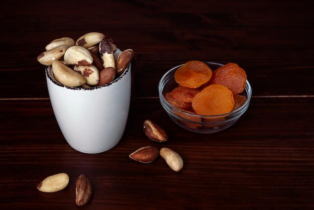 Miski z orzechami brazylijskimi i suszonymi morelami na drewnianym stole. koncepcja suszonych owoców i orzechów