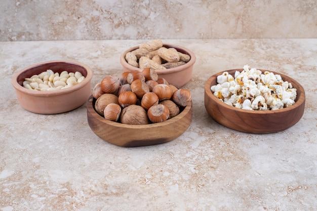 Miski z orzechów laskowych, orzeszków ziemnych, pestek słonecznika i popcornu na marmurowej powierzchni