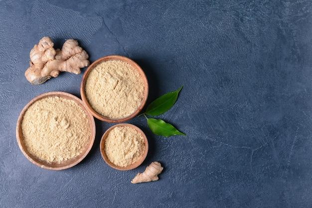 Miski z proszkiem imbirowym i korzeniami na kolor