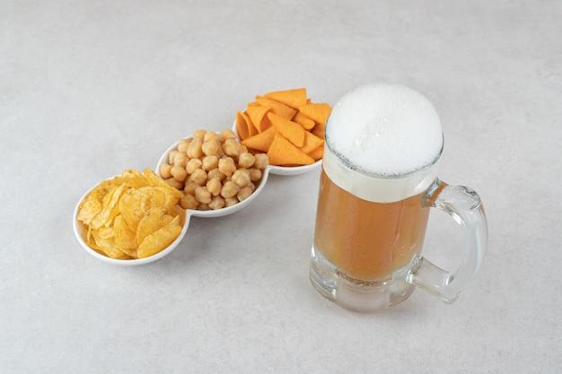 Miski z przekąskami i szklanka piwa na kamiennej powierzchni