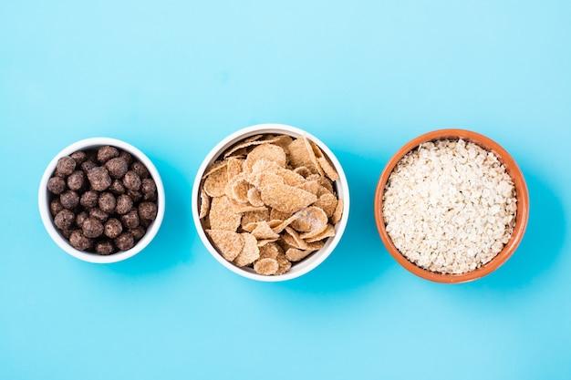 Miski z różnymi rodzajami śniadań: płatki owsiane, płatki zbożowe i kulki czekoladowe na jasnoniebieskim stole. widok z góry