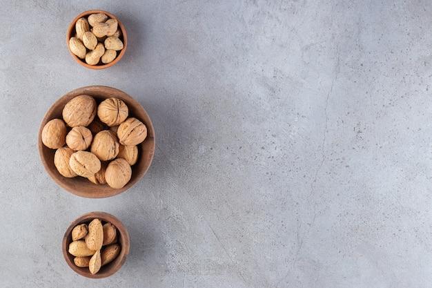 Miski z różnymi rodzajami zdrowych orzechów umieszczonych na kamiennym tle.