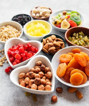 Miski z różnymi suszonymi owocami i orzechami na szarej betonowej powierzchni