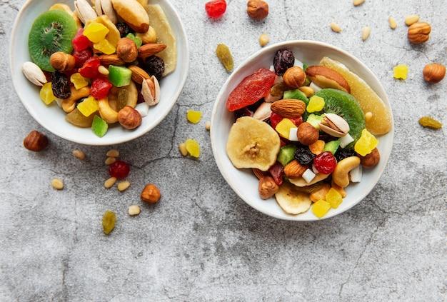 Miski z różnymi suszonymi owocami i orzechami na szarym tle betonu