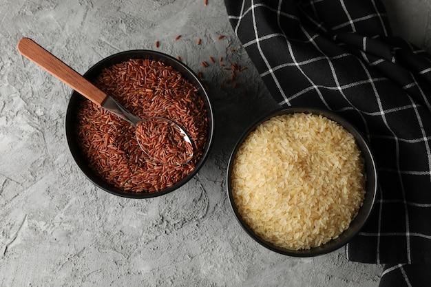 Miski z ryżem, łyżką i ręcznikiem na szarej powierzchni