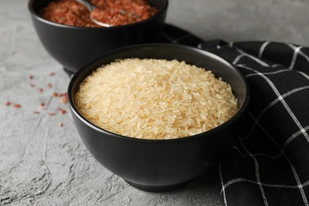 Miski z ryżem, łyżką i ręcznikiem na szarym stole