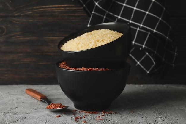 Miski z ryżem, ręcznikiem i łyżką na szarym stole