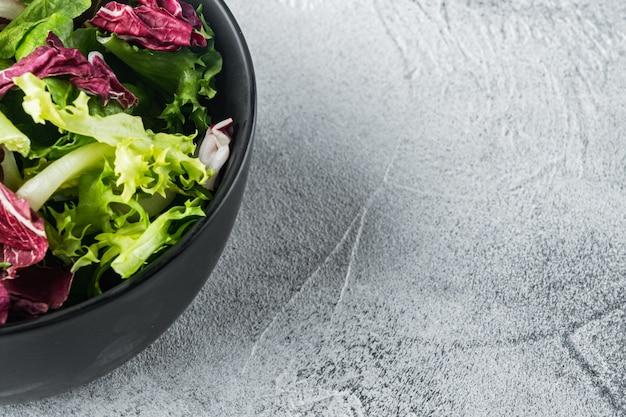 Miski z sałatą mieszaną rozdrobnioną świeżymi liśćmi, na szarym tle