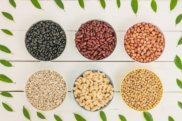 Miski z soi, czarnej fasoli, fasoli czytanej, orzeszków ziemnych, orzechów nerkowca i prosa na białym stole.