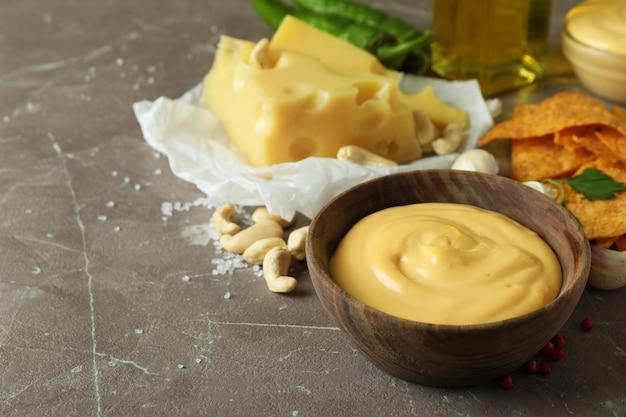 Miski z sosem serowym i składnikami na szarym teksturowanym stole