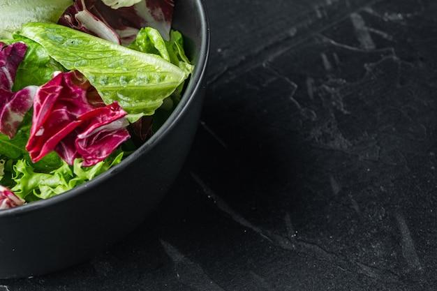 Miski z świeżych liści sałaty mieszanej rozdrobnione, na czarnym tle z miejsca kopiowania tekstu