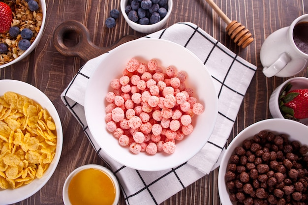 Miski z truskawkami, czekoladowymi kuleczkami ze słodkiej kukurydzy, musli i płatkami kukurydzianymi z jagodami. pyszne i zdrowe płatki śniadaniowe. widok z góry.