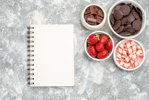 Miski z widokiem z góry z truskawkowymi cukierkami i czekoladkami oraz notes na szaro-białym podłożu
