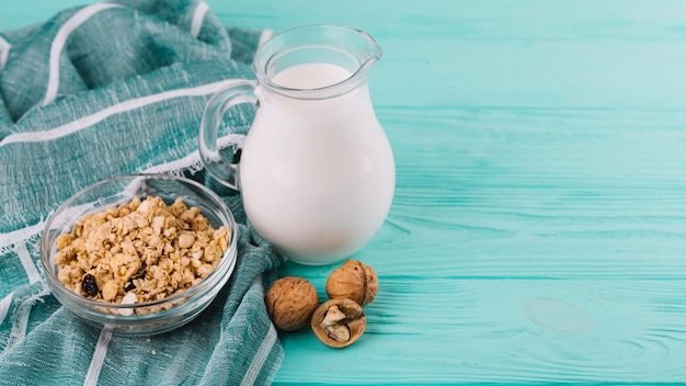 Miski zbóż; słoik mleka i orzechy włoskie na zielony drewniany stół z tkaniny