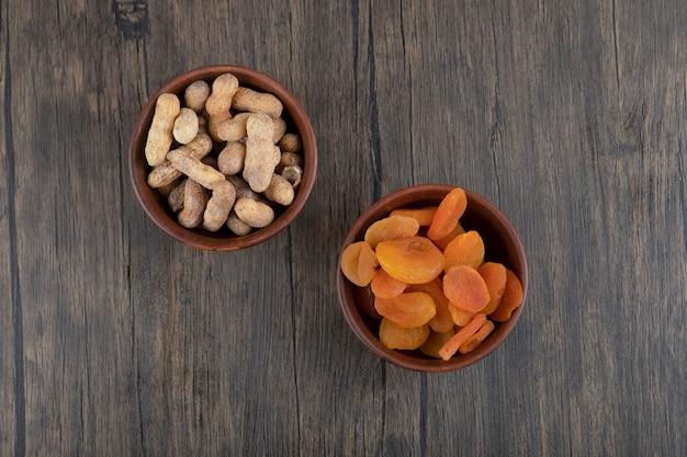 Miski zdrowych suszonych owoców moreli i orzeszków ziemnych w łupinach na drewnianym stole.