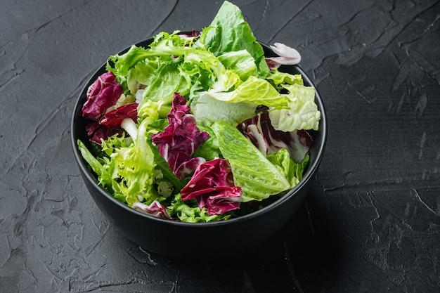 Miski ze świeżymi liśćmi sałaty mieszanej rozdrobnionej, na czarnym stole