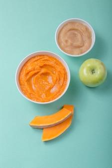 Miski ze zdrowym jedzeniem dla niemowląt na stole kolorów. puree, wykonane ze świeżych organicznych owoców i warzyw, leżał flay, widok z góry, koncepcja. posiłek dla dzieci