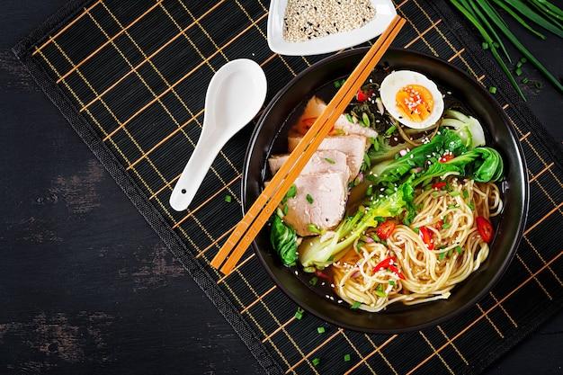 Miso ramen azjatycki makaron z jajkiem, wieprzowiną i kapustą pak choi w misce. kuchnia japońska. widok z góry. leżał płasko