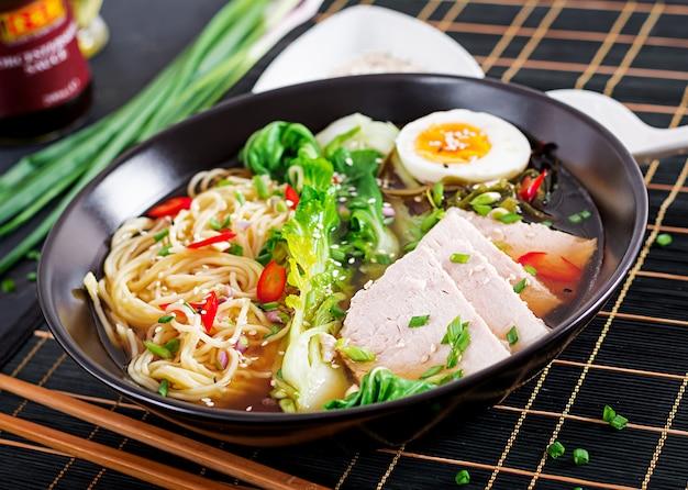 Miso ramen azjatycki makaron z jajkiem, wieprzowiną i kapustą pak choi w misce. kuchnia japońska.