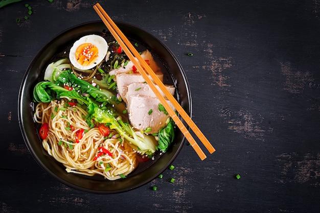 Miso ramen azjatycki makaron z jajkiem, wieprzowiną i kapustą pak choi w misce na ciemnej powierzchni. kuchnia japońska.
