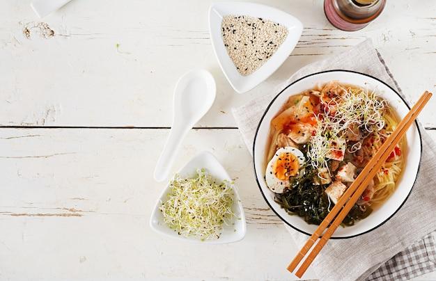 Miso ramen azjatycki makaron z kimchi kapustą, wodorostami, jajkiem, pieczarkami i tofu z serem w misce na białym drewnianym stole.