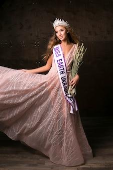 Miss earth kobieta w koronie, wstążce i kłoskach pszenicy. konkurs mody, piękna modelka pozowanie