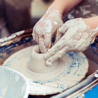 Mistrz ceramiki tworzy kształty z gliny.