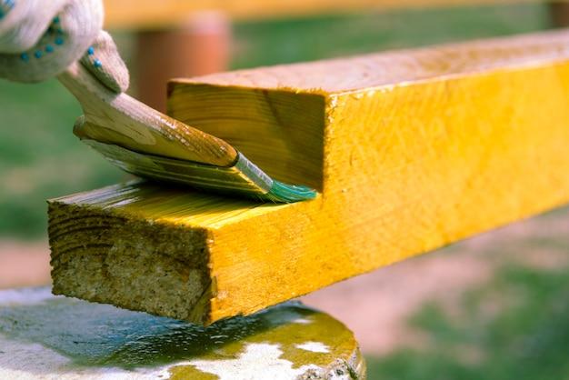 Mistrz cieśli pędzlem maluje deski z ochroną przed wilgocią, gniciem. obróbka drewna opałowego. budowa domu