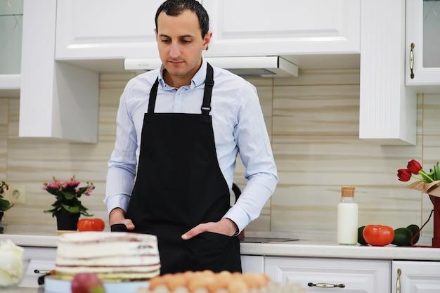 Mistrz cukiernictwa przed biurkiem. gotowanie deserów w domu. armeńczyk zajmuje się słodyczami.