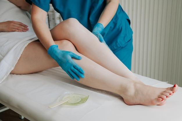 Mistrz cukrowania nakłada puder na nogi podczas depilacji