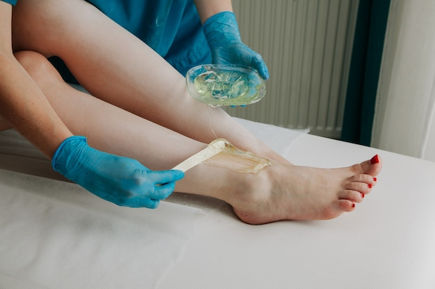 Mistrz cukrowania nakłada wosk do depilacji na nogi