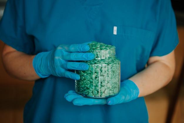 Mistrz depilacji trzymający w przezroczystym słoiczku niebieskie woskowe krople pasty słodzącej.