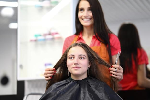 Mistrz fryzjerski trzyma włosy klienta w salonie kosmetycznym