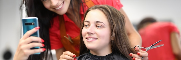 Mistrz fryzjerski z klientem patrzy na ekran smartfona w salonie kosmetycznym.